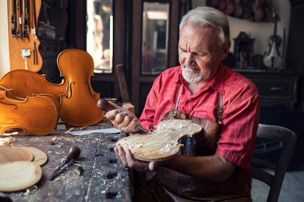 Carpintero senior artesano tallando madera en su antiguo taller de moda