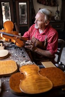 Carpintero senior comprobando el instrumento de violín que está a punto de reparar