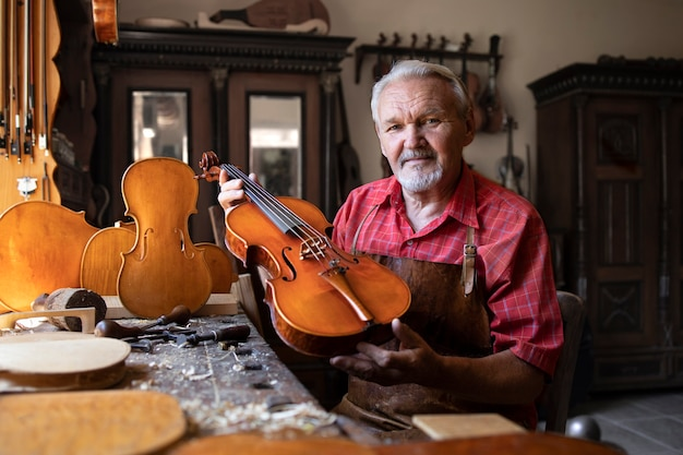 Carpintero senior mostrando el instrumento de violín que creó