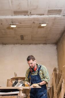 Carpintero de sexo masculino profesional que toma la medida en el banco de trabajo en taller