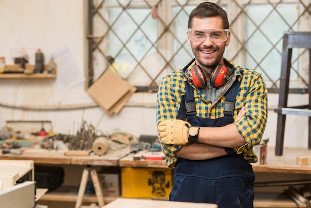 Carpintero de sexo masculino sonriente que lleva las gafas de seguridad que se colocan delante de la mesa de trabajo con su brazo cruzado