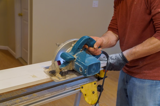 Carpintero con sierra circular para cortar tablas con herramientas eléctricas manuales.