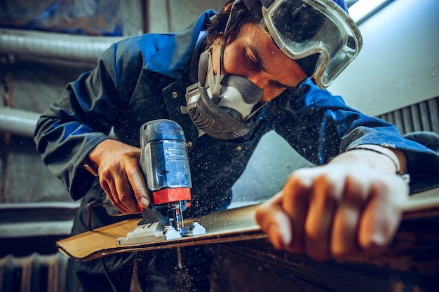 Carpintero con sierra circular para cortar tablas de madera. detalles de construcción de trabajador masculino o hombre práctico con herramientas eléctricas