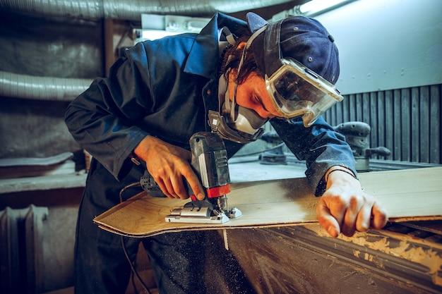 Carpintero con sierra circular para cortar tablas de madera