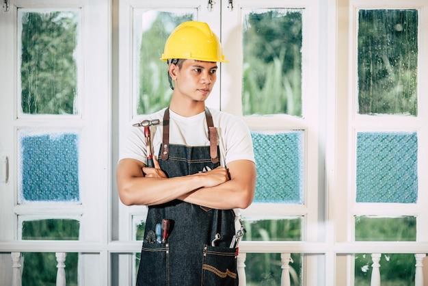 El carpintero se para y sostiene un martillo.