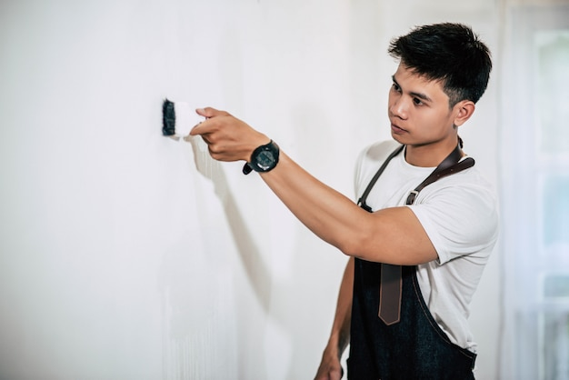 Un carpintero sostiene un pincel y pinta madera.