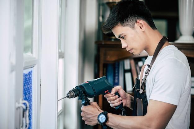 El carpintero sostiene el taladro y taladra la ventana.