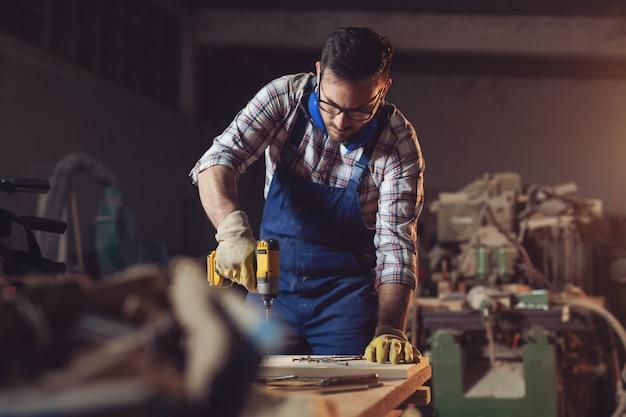 Carpintero taladra un agujero con un taladro eléctrico