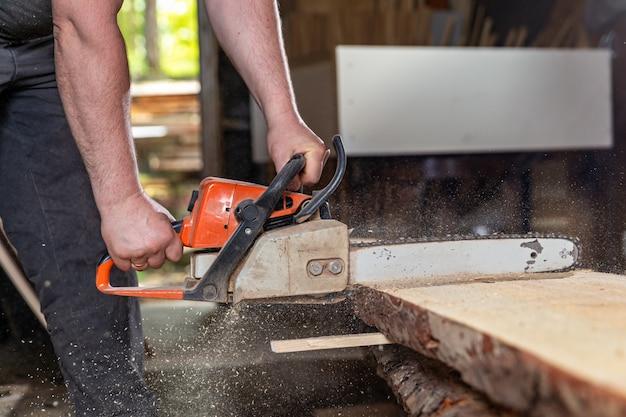 Carpintero tallado en madera con motosierra manual