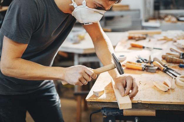 El carpintero trabaja con un arbol.