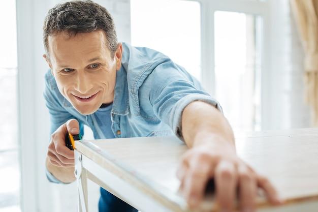 Carpintero trabajador. la atención se centra en un apuesto joven carpintero que usa una cinta métrica y calcula el ancho de una mesa.