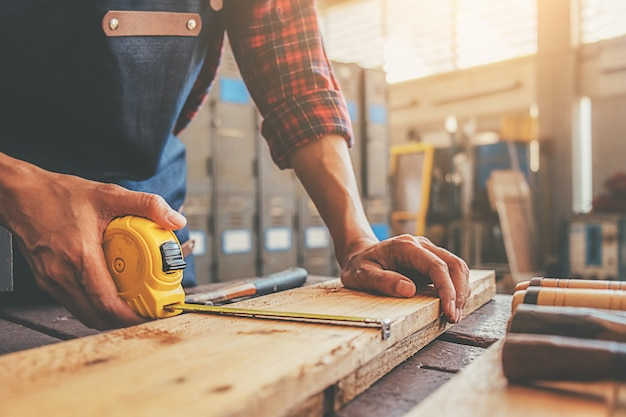 Carpintero trabajando con equipo en mesa de madera en taller de carpintería