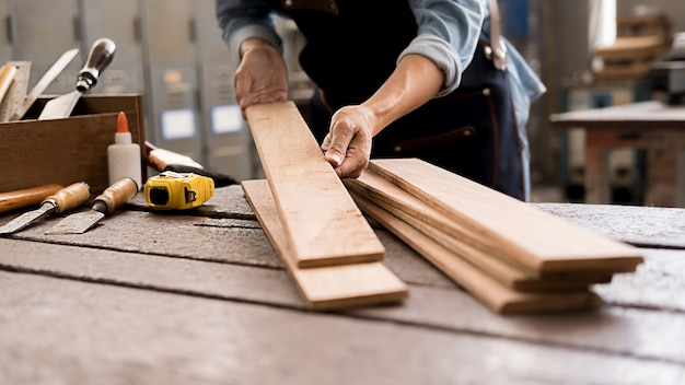 Carpintero trabajando con equipos en la mesa de madera en la tienda de carpintería. la mujer trabaja en un taller de carpintería.