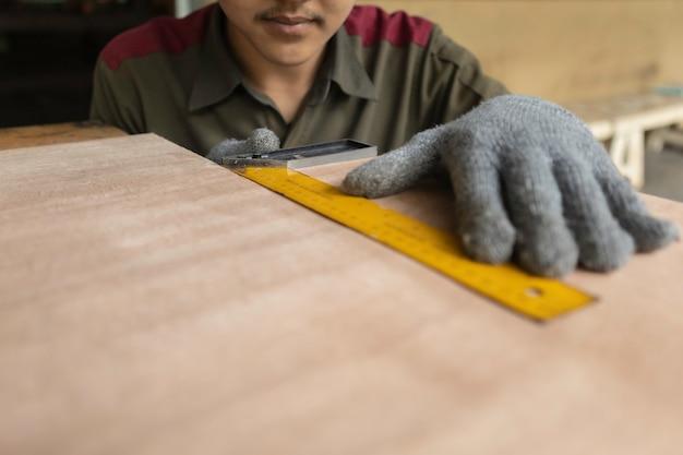 Carpintero trabajando en máquinas de carpintería en taller de carpintería. carpintero experto cortando un trozo de madera en su taller de carpintería.