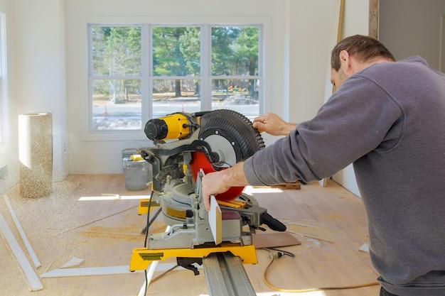 Carpintero en el trabajo usando sierra circular cortando molduras de madera zócalo
