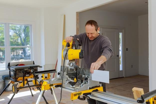 Carpintero utilizando una sierra circular para cortar tablero de madera