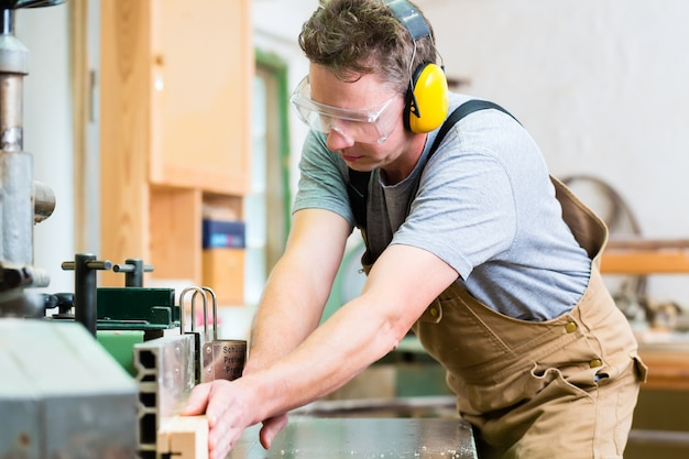 Carpintero utilizando sierra eléctrica en carpintería.