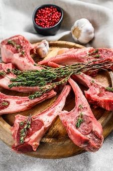 Carré de cordero, carne cruda con hueso, chuletas con sal, pimienta