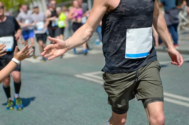 Carrera de maratón, apoyo de los corredores en la carrera de ruta, mano del niño dando cinco años, apoyo de los atletas que corren, concepto deportivo