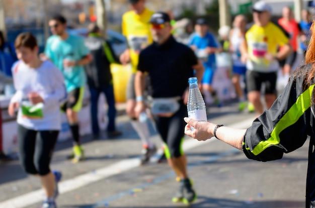 Carrera de maratón, corredores en ruta, voluntario dando agua en el punto de refrigerio