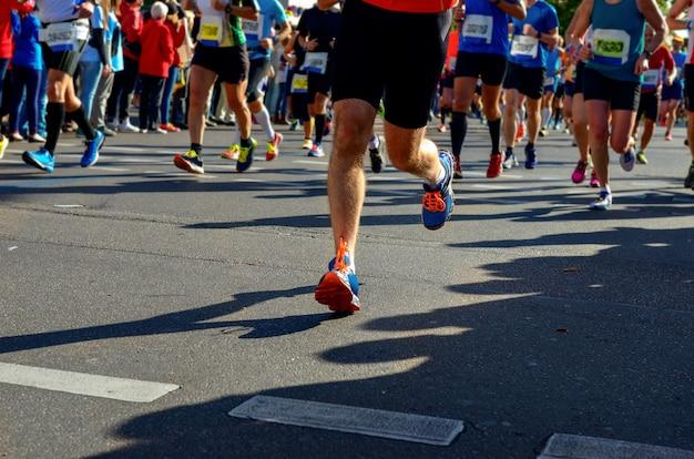 Carrera de maratón, muchos corredores pies en carreras de carretera