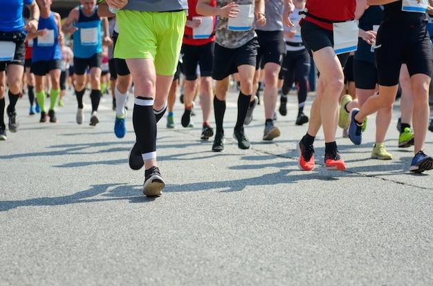 Carrera de maratón, muchos pies de corredores en carreras de carretera, competición deportiva, fitness y concepto de estilo de vida saludable