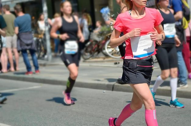 Carrera de maratón, mujer corredora en carreras de carretera, competición deportiva, fitness y concepto de estilo de vida saludable