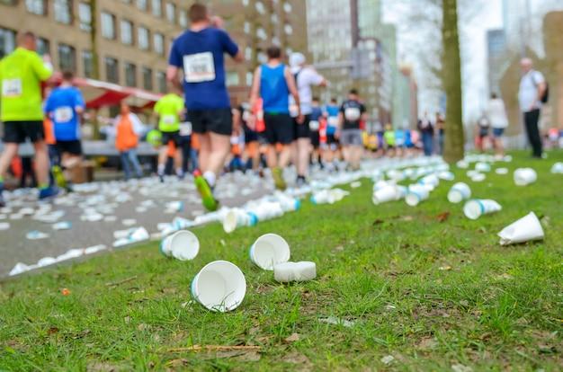 Carrera de maratón, pies de corredores y vasos de agua de plástico en la carretera cerca del punto de refrigerio, deporte, fitness y concepto de estilo de vida saludable
