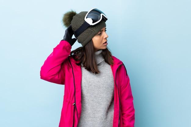Carrera mezclada, esquiador, mujer, con, snowboard, anteojos, encima, aislado, pared azul, teniendo, dudas, mientras, rascar, cabeza