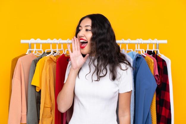 Carrera mezclada, mujer, en, un, tienda de ropa, gritos, con, boca bien abierta