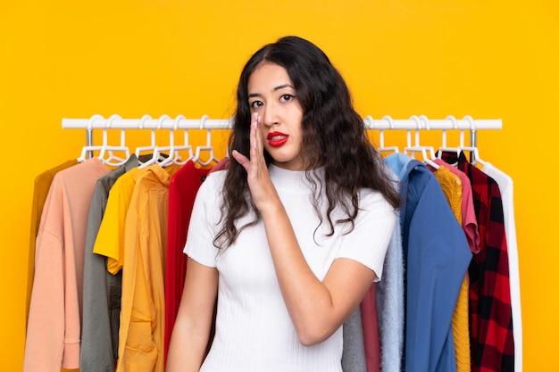 Carrera mezclada, mujer, en, un, tienda de ropa, susurrando algo