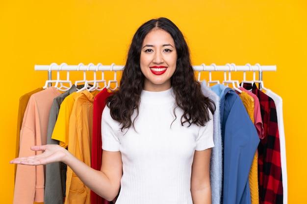 Carrera mezclada, mujer, en, un, tienda de ropa, tenencia, copyspace, imaginario, en la palma