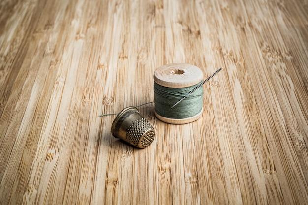 Carrete antiguo de hilo de color con aguja para coser y dedal vintage sobre fondo de madera, mesa de trabajo de sastre.