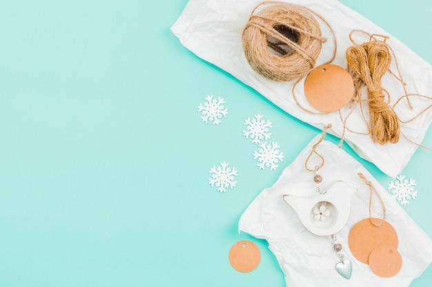 Carrete de cuerda de yute; círculo de papel y copo de nieve para hacer colgar en la pared sobre fondo turquesa