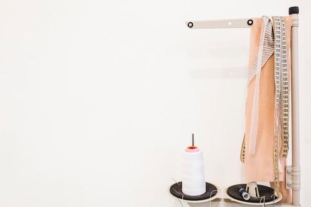 Carrete de hilo blanco además de cinta métrica y tela en la tienda
