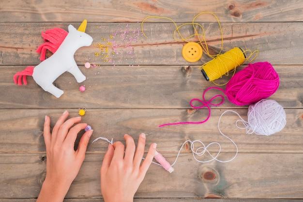 Carrete de hilo amarillo; lana; hilo y abalorios con unicornio en mesa de madera.