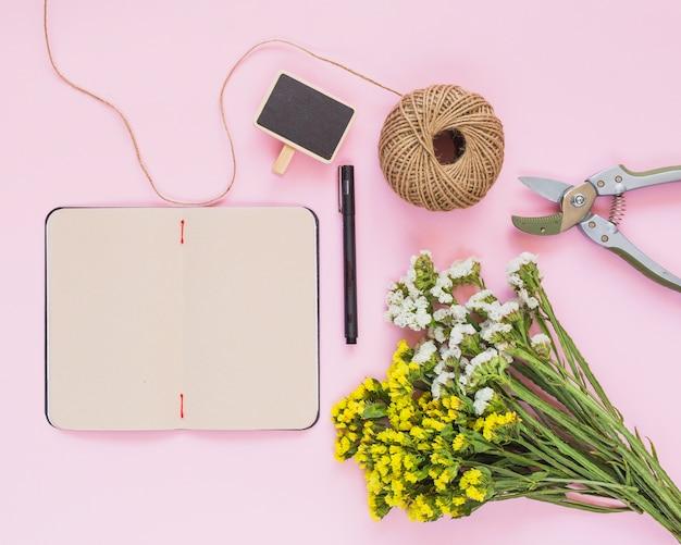 Carrete de hilo; bolígrafo; etiqueta; diario; flores y tijeras de jardín contra fondo rosa.