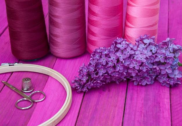 Carrete de hilo rojo en un marco de bordado de madera en la mesa rosa