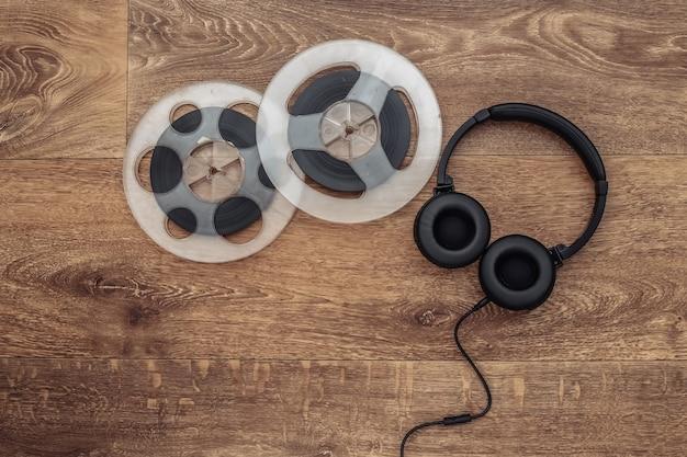 Carrete magnético de audio retro y auriculares estéreo sobre fondo de madera. vista superior. endecha plana