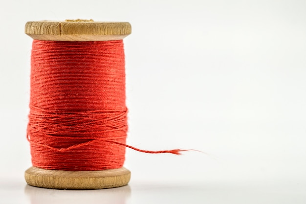 Carrete o carrete de hilo de coser rojo aislado en blanco. poca profundidad de campo. primer plano macro disparo.