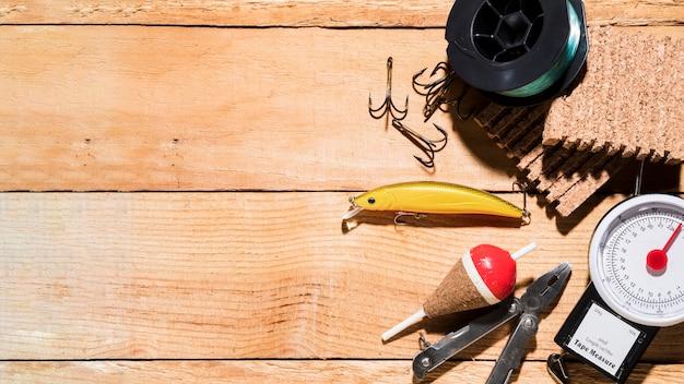 Carrete de pesca; señuelo de pesca; flotador de pesca alicate tablero de corcho y balanza sobre mesa