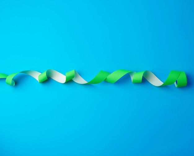 Carrete sin torcer con adhesivos adhesivos verdes sobre un fondo azul.