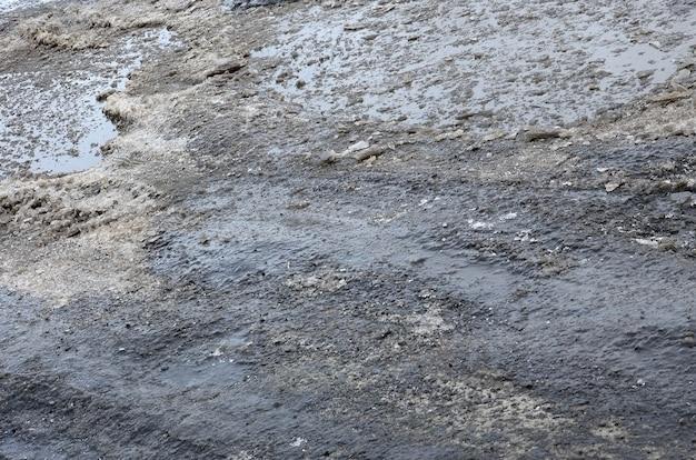 Carretera asfaltada dañada con baches causados por el congelamiento.