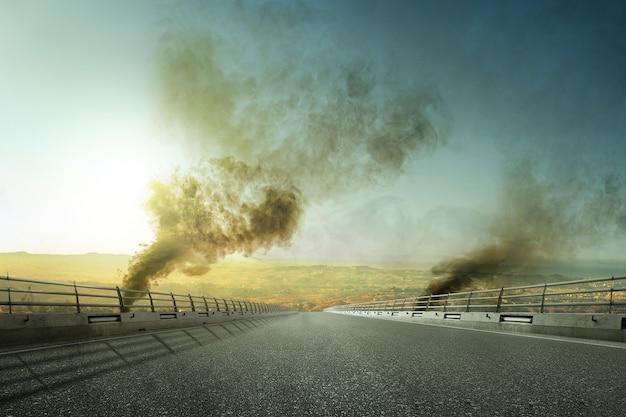 Carretera asfaltada con humo oscuro y contaminación del aire por incendios forestales