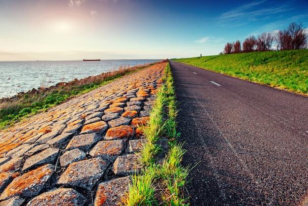 Carretera asfaltada junto al mar al atardecer