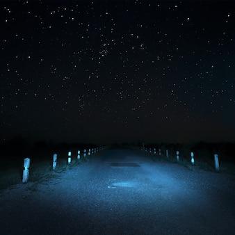 Carretera asfaltada local en la noche con fondo de estrellas y sin iluminación de la calzada