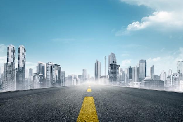 Carretera asfaltada vacía hacia ciudad moderna.
