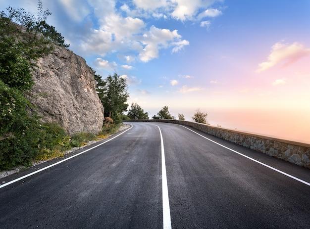 Carretera de asfalto en el bosque de verano al atardecer. montañas de crimea