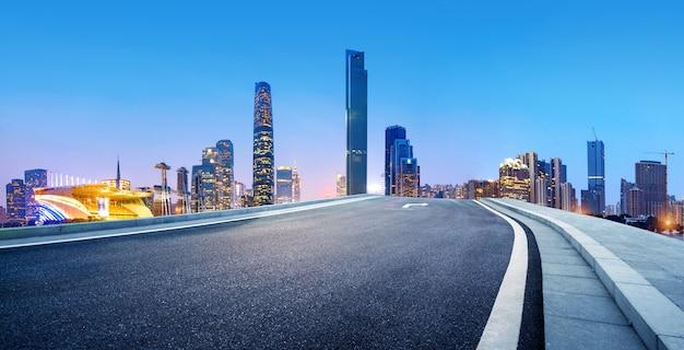 Carretera de asfalto junto a edificio moderno.