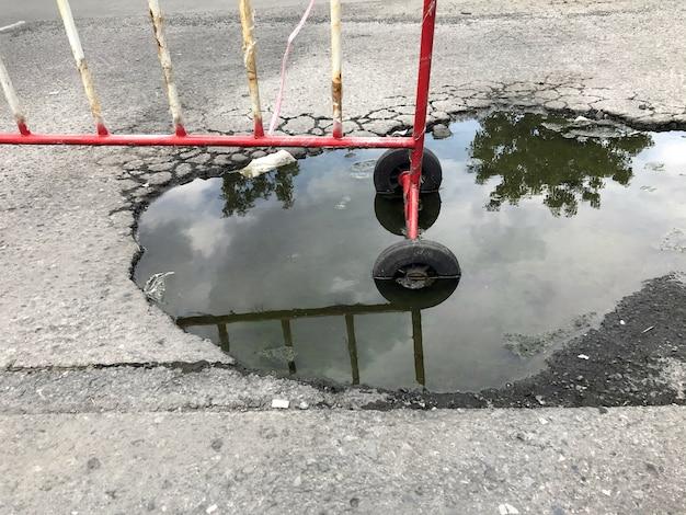 Carretera de asfalto rota con agua, sin zona de paso